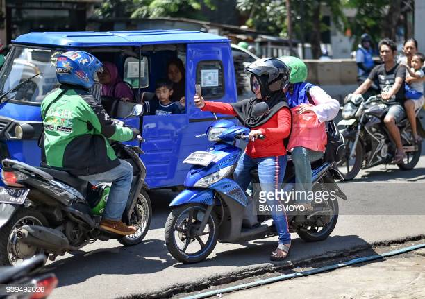 Indonesian women take a selfie as they sit on a motorbike in traffic on a road in Jakarta on March 29 2018 / AFP PHOTO / BAY ISMOYO