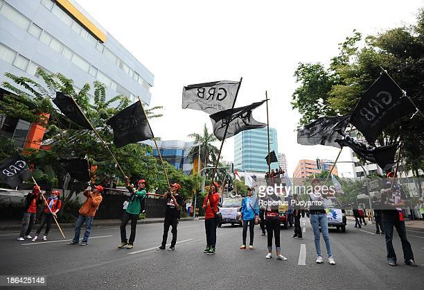 Indonesian workers and labor unions march down the road during a protest demanding higher wages on October 31 2013 in Surabaya Indonesia Several...