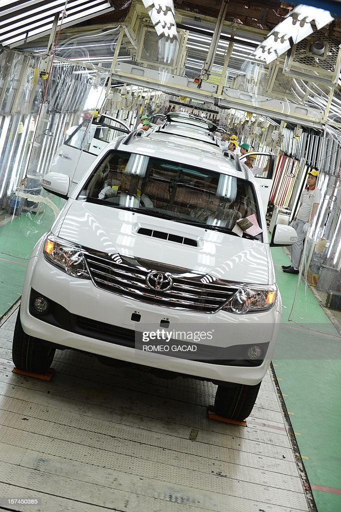 Indonesian workers roll out Toyota vehicles at the assembly line of Toyota Motor's Indonesian unit, Toyota Motor Manufacturing Indonesia (TMMIN) plant in Karawang industrial center outside Jakarta on December 3, 2012. Japan's Toyota group announced in Tokyo on November 10, 2012 that it will invest about 1.3 billion USD over the next five years in expanding its vehicle production in Indonesia. Toyota Motor and its five affiliated firms are making the move 'considering the remarkable growth of the (Indonesian) market in recent years.'