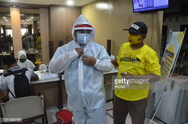 Indonesian workers with one wearing a shirt reading reject omnibus law donate personal protective equipment to a local hospital as part of their...