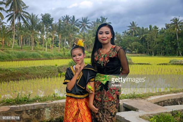 Indonesian young woman and girl in beautiful traditional dress in the rice fields near Tetebatu on the island Lombok Indonesia