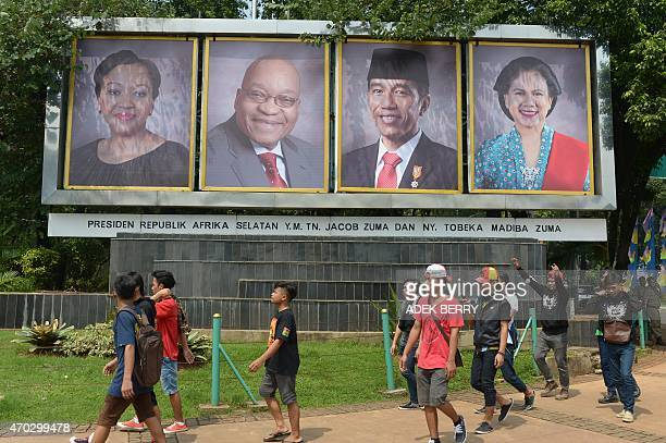 Indonesian youth walk past posters of Indonesian President Joko Widodo First Lady Iriana Widodo South African President Jacob Zuma and his spouse...