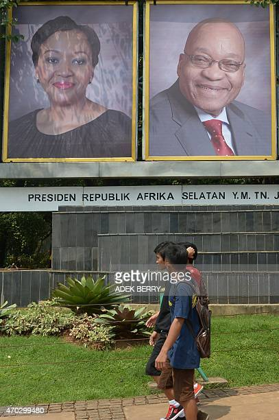 Indonesian youth walk past posters of South African President Jacob Zuma and his spouse Thobeka Madiba Zuma in Jakarta on April 19 2015 South African...