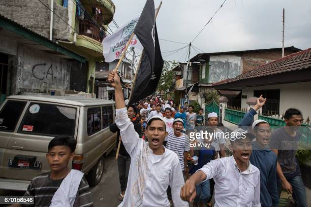 Indonesian youths march through their neighbourhood with an Islamic flag after quick count results showed their favoured candidate decisively ahead...