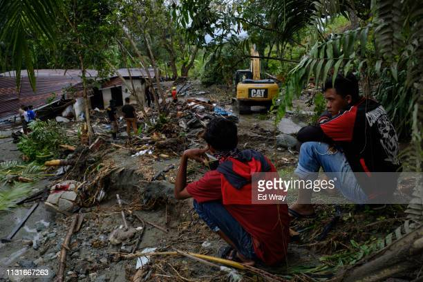 Indonesian youths watch as search and rescue teams look for the remains of victims trapped under debris on March 20 2019 in Sentani Papua province...