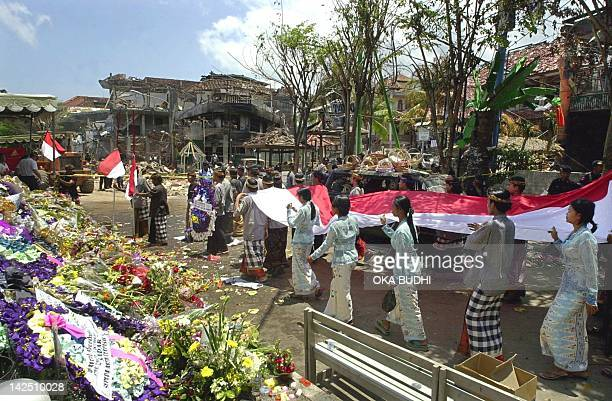 Indonesians carry a long national flag as they walk to the 12 October blast site at Kuta near Denpasar 20 October 2002 The number of people confirmed...