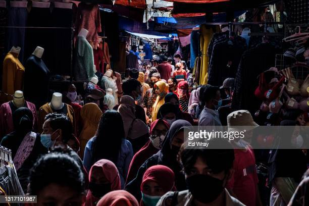 Indonesians crowd a traditional textile market to buy clothes before the Eid Al Fitr holiday which comes next week on May 09, 2021 in Jakarta,...