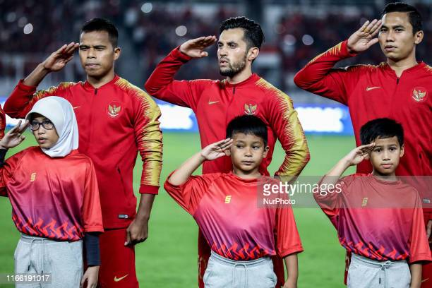 Indonesian's Manahati Lestusen Stefano Lilipaly and Ricky Fajrin Saputra sing National Anthem during FIFA World Cup 2022 qualifying match between...