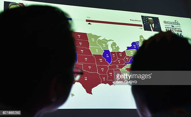 Indonesians observe a US electoral map as they wait for the results of the country's presidential election during an event organised by the US...