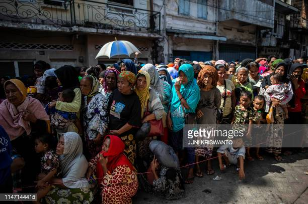 TOPSHOT Indonesians queue up for charitable cash handouts in Surabaya on May 31 ahead of Eid alFitr marking the end of the holy fasting month of...