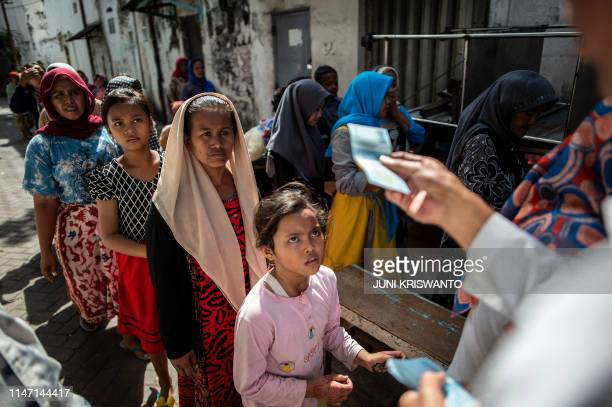 Indonesians queue up for charitable cash handouts in Surabaya on May 31 ahead of Eid alFitr marking the end of the holy fasting month of Ramadan