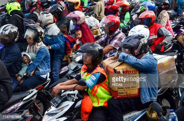 Indonesians ride their motorcycles in Bekasi on the outskirts of Jakarta on May 31 during Indonesia's mass moving of Muslim people to their...