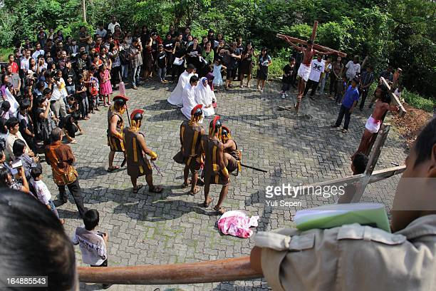 Indonesians take part in a reenactment of the Stations Of The Cross on Good Friday at the Raja Agung church on March 29 2013 in Bintan Island...