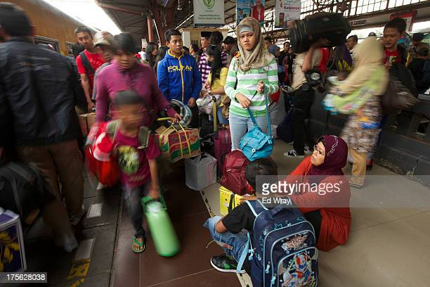Indonesians wait for a train which will take them to their home villages for the August 8 Eid al Fitr holiday on August 5 2013 in Jakarta Indonesia...
