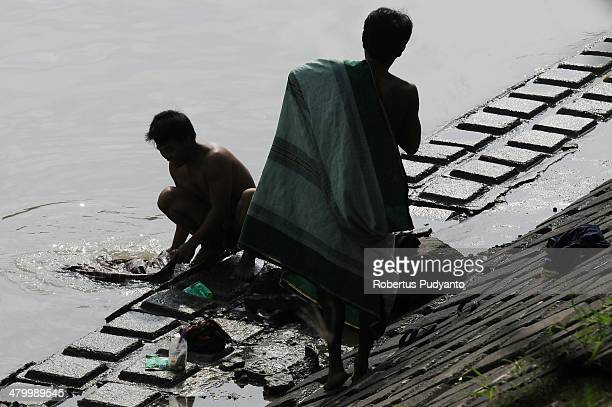Indonesians wash their clothes in a polluted river on World Water Day March 22 2014 in Surabaya Indonesia World Water Day recognizes the global need...