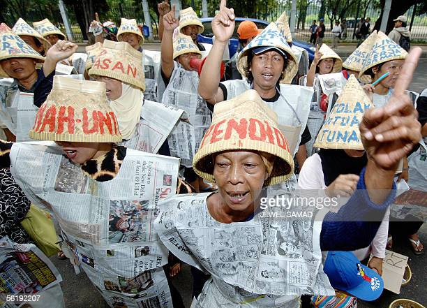 Indonesians wear jersey made out of newspapers as they shout antigovernment slogans during a demonstration against the fuel price hike in front of...