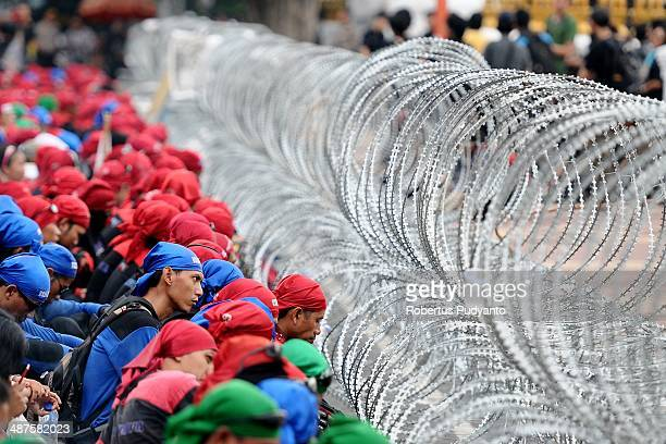 Indonesians workers sit behind barbedwire during a protest demanding higher wages on May Day on May 1 2014 in Surabaya Indonesia Protesters across...