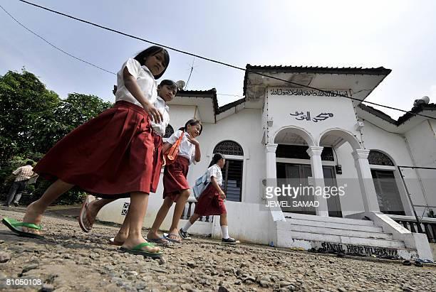 STORY IndonesiaPoliticsReligionIslam by Aubrey Belford School girls walk past a mosque belonging to Ahmadiyah sect of Muslim in Ciaruteun Bogor on...