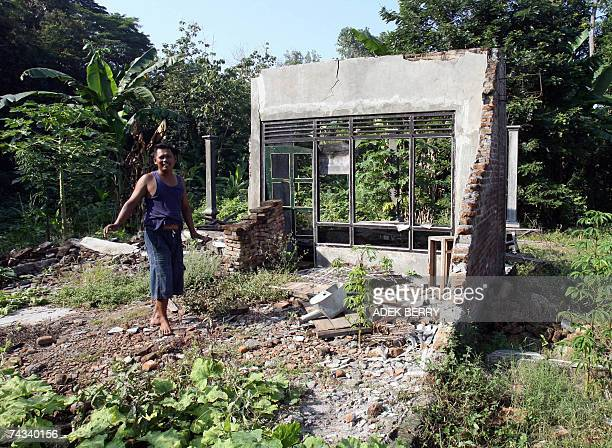 STORY 'Indonesiaquake1yearhousingdomesched' A man shows a destroyed house in the old part of Ngelepen village in Bantul 20 May 2007 nearby the New...