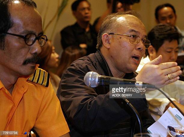 Indonesia's Air Transport Director General Mohammad Iksan Tatang gestures as he talks to journalists next Adam Air's Operation Director Captain...