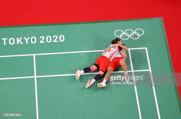 Indonesia's Apriyani Rahayu and Indonesia's Greysia Polii celebrate after winning their women's doubles badminton final match against China's Jia...