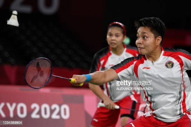 Indonesia's Apriyani Rahayu hits a shot next to Indonesia's Greysia Polii in their women's doubles badminton final match against China's Jia Yifan...