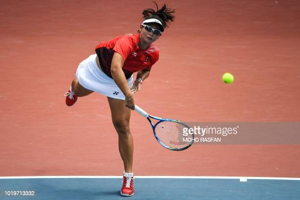 Indonesia's Beatrice Gumulya serves against India's Ankita Ravinderkrishan Raina in their womens's singles tennis match during the 2018 Asian Games...