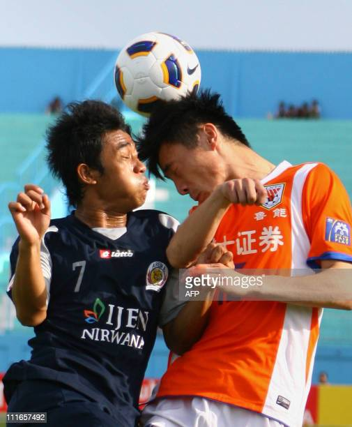 Indonesia's Benny Wahyudi of Arema Indonesia and China's Zheng Zheng of Shandong Luneng FC fight for the ball during their AFC Champions League game...
