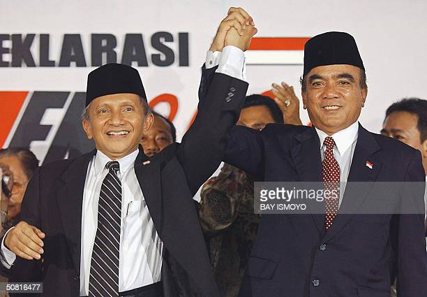 Indonesia's Consultative Assembly Chairman Amien Rais raises hands with the head of the country's farmer's association Siswono Yudhohusodo at a...