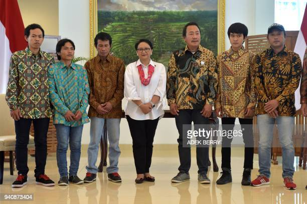 Indonesia's Foreign Minister Retno Marsudi poses with recently released hostages from Libya at a government handover ceremony reuniting them upon...