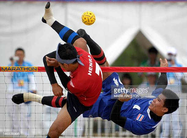 Indonesia's Hendra Pago tries to block a shot from Thailand's Uthen Kukheaw during their men's team Sepak Takraw match at the 3rd Asian Beach Games...