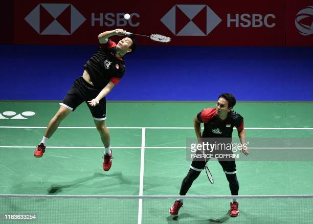 Indonesia's Hendra Setiawan next to teammate Mohammad Ahsan returns a shuttlecock to Indonesia's Muhammad Rian Ardianto and Fajar Alfian during their...