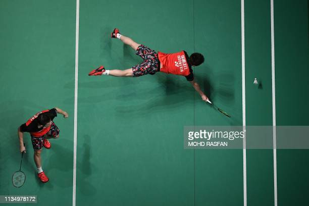 Indonesia's Kevin Sanjaya Sukamuljo dives for a return while teammate Marcus Fernaldi Gideon looks on during their men's doubles quarterfinal match...