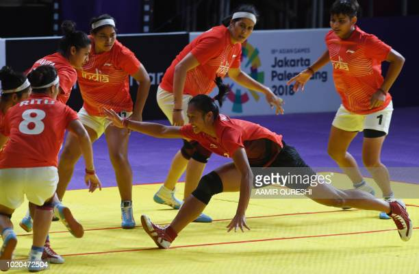 Indonesia's Laraswati Ni Putu Dewi tries to a score as India's players defend during the women's team Group A kabaddi match between India and...