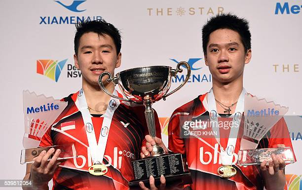 Indonesia's Marcus Fernaldi Gideon and Kevin Sanjaya celebrate with the championship trophy after beating Indonesia's Angga Pratama and Ricky Karanda...