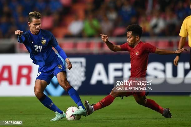 Indonesia's midfielder Andik Vermansah fights for the ball with Thailand's midfielder Sanrawat Dechmitr during the AFF Suzuki Cup 2018 football match...