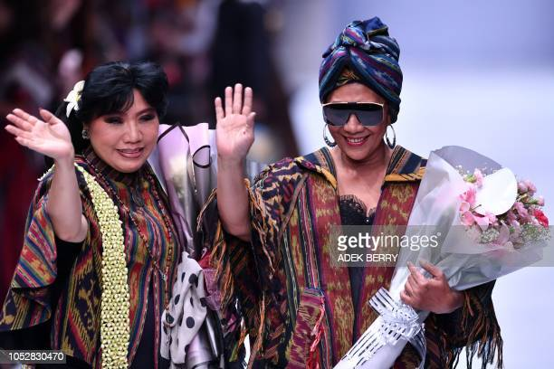 Indonesia's Minister of Maritime Affairs and Fisheries Susi Pudjiastuti and designer Anne Avantie wave to the audience as the minister participates...