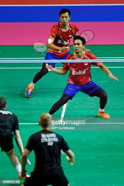 Indonesia's Mohammad Ahsan and Rian Agung Saputro return to Denmark's Mathias Christiansen and David Daugaar during their round three men's doubles...