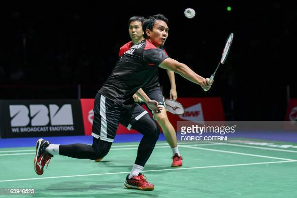 Indonesia's Mohammad Ahsan , next to Indonesia's Hendra Setiawan, returns a shuttlecock to Japan's Yugo Kobayashi and Japan's Takuro Hoki during of...