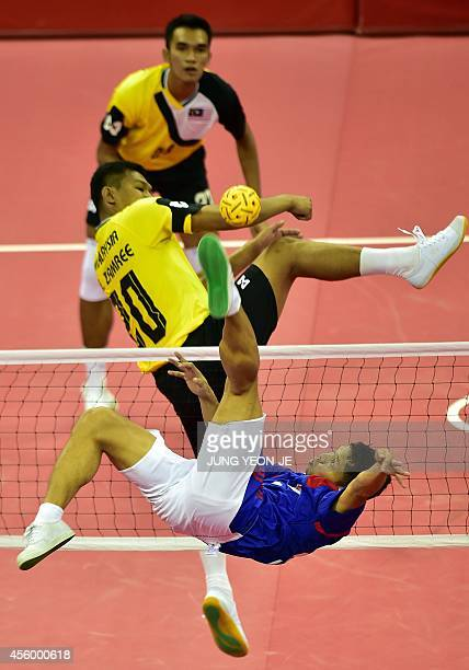 Indonesia's Nofrizal strikes the ball against Malaysia's Mohd Zamree Bin Mohd Dahan in the men's team sepaktakraw preliminary match during the 2014...