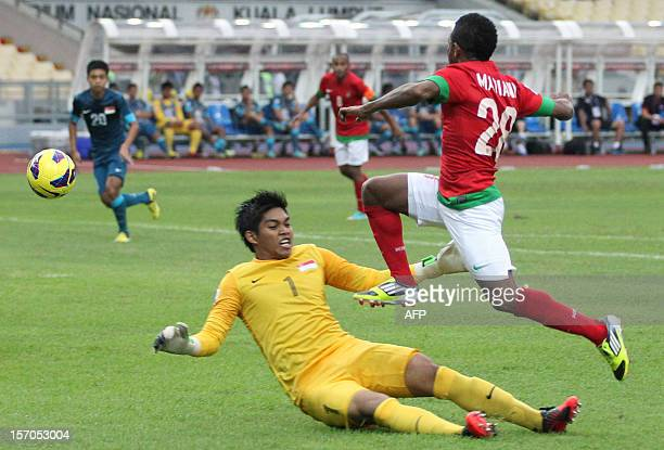 Indonesia's player Oktovianus Maniani tries to shoot past Singapore's goalkeeper Izwan Mahbud during their AFF Suzuki Cup group B football match in...