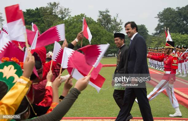 TOPSHOT Indonesia's President Joko Widodo and Emir of Qatar Tamim bin Hamad alThani look at children waving both country's flags during a welcome...