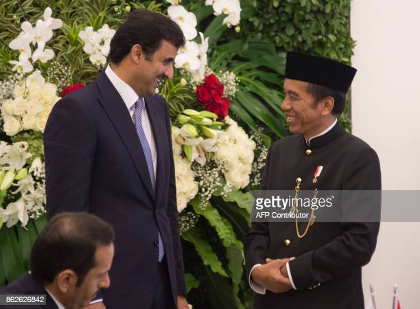 Indonesia's President Joko Widodo and Emir of Qatar Tamim bin Hamad alThani share a light moment before a joint press conference at the presidential...