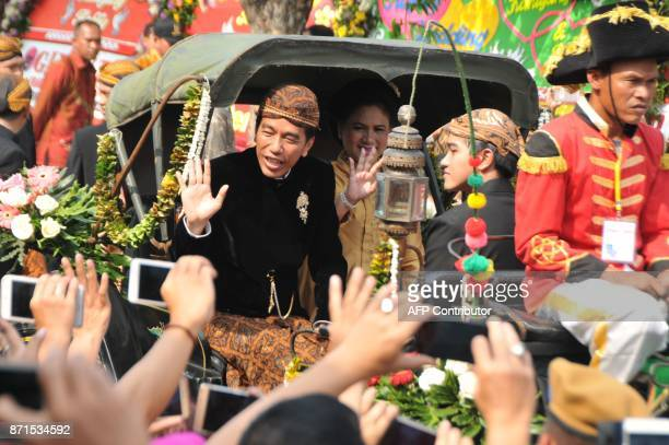 Indonesia's President Joko Widodo and First Lady Iriana Widodo wave to wellwishers during a wedding procession for their daughter Kahiyang Ayu's...