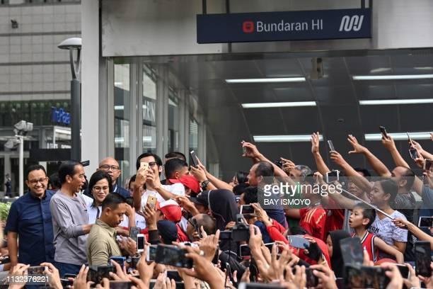 Indonesia's President Joko Widodo greets people gathered outside the Bundaran HI mass rapid transit station during the inauguration of Jakarta's new...