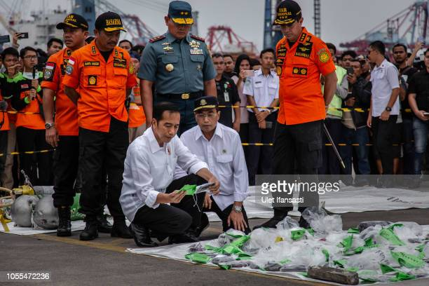 Indonesia's President Joko Widodo holds a personal item from Lion Air flight JT 610 at the Tanjung Priok port on October 30 2018 in Jakarta Indonesia...