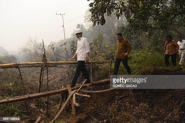 Indonesia's President Joko Widodo is followed by Disaster Management Agency chief Willem Rampangilei Environment Minister Siti Nurbaya Bakar and...