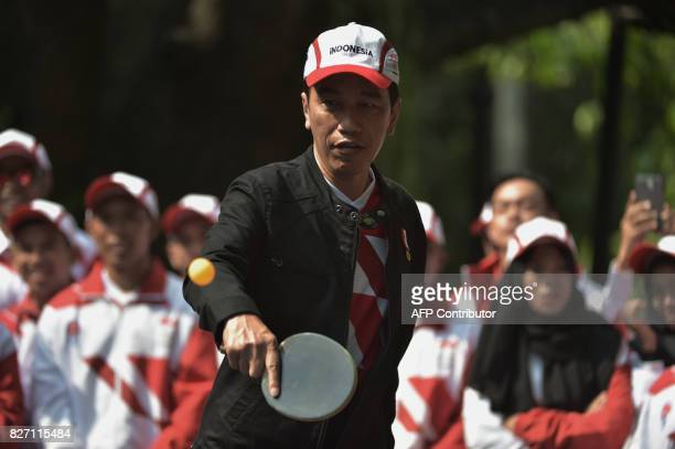 Indonesia's President Joko Widodo plays table tennis as Indonesian athletes look on after a ceremony at the presidential palace in Jakarta on August...