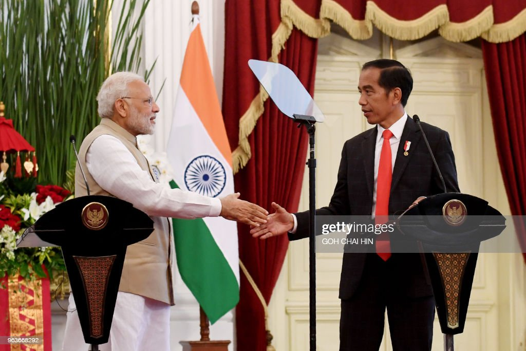 Indonesia's President Joko Widodo (R) shakes hands with India's Prime Minister Narendra Modi during a joint press conference at the presidential palace in Jakarta on May 30, 2018.