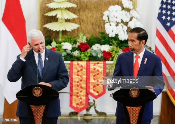 Indonesia's President Joko Widodo speaks to the media as US Vice President Mike Pence adjusts his earphone during a press conference at Merdeka...